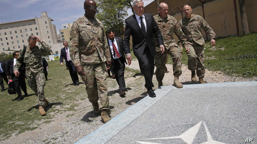 U.S. Defense Secretary James Mattis, third right, walks with U.S. Army Command Sergeant Major David Clark, left, and General Christopher Haas, second right, as he arrives to the Resolute Support headquarters in Kabul, Afghanistan, April 24, 2017.