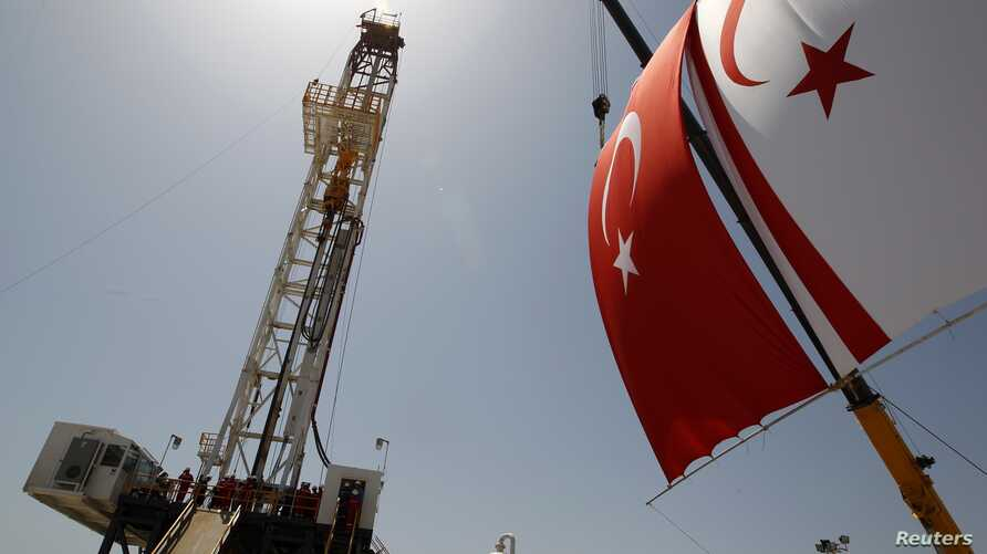 Turkish and Turkish Cypriot flags wave beside a offshore drilling tower near Famagusta, Cyprus, April 26, 2012.