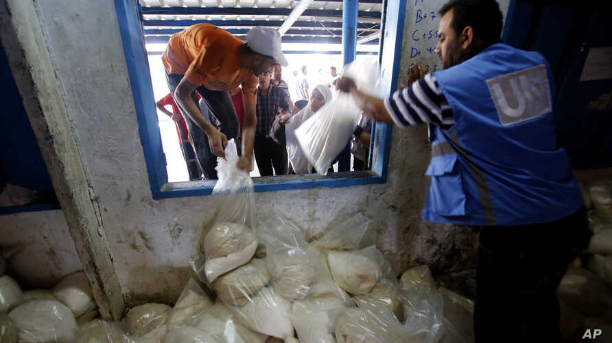 Palestinians crowd a window for food aid at a United Nations distribution center in the Shati refugee camp in Gaza City, Aug. 6, 2014.