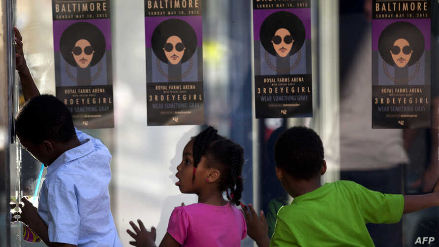 """Children look through glass as fans of musician Prince enter a """"Rally 4 Peace"""" concert in Baltimore, Maryland, May 10, 2015."""