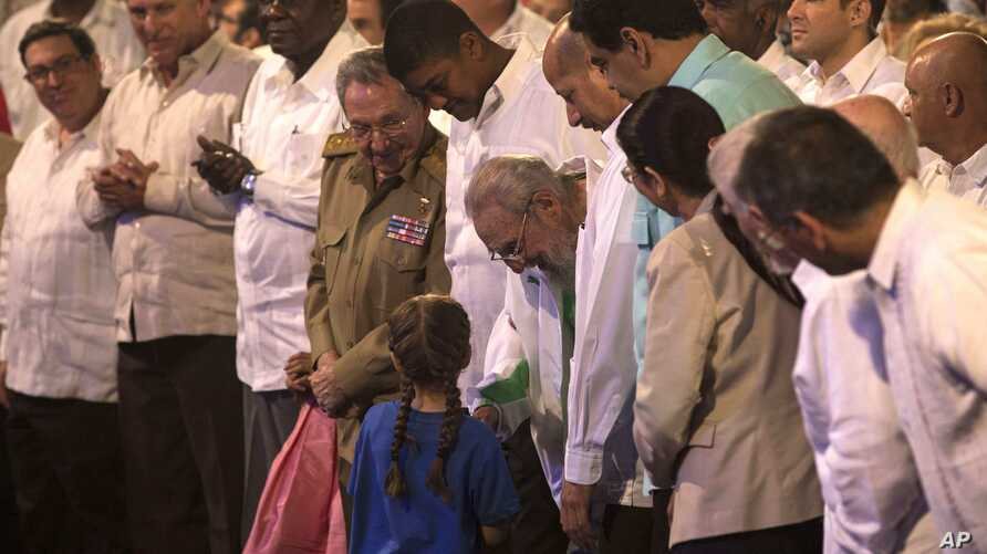 Cuban Leader Fidel Castro, center, talks with a girl during a gala for his 90th birthday at the 'Karl Marx' theater in Havana, Cuba, Saturday, Aug. 13, 2016.