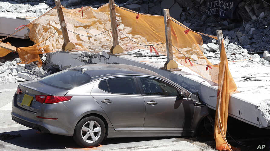 A crushed car is shown under a section of a collapsed pedestrian bridge, Friday, March 16, 2018 near Florida International University in the Miami area.