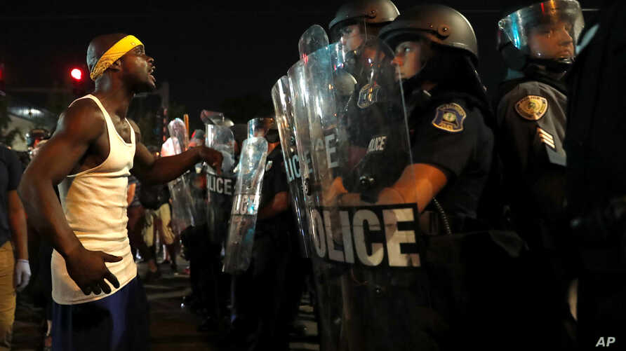 A man yells at police in riot gear just before a crowd turned violent, Sept. 16, 2017, in University City, Mo.