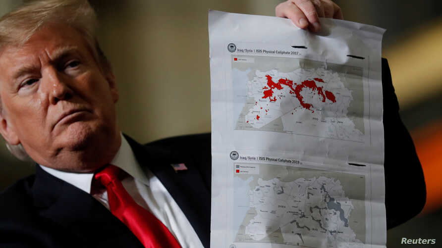 "President Donald Trump shows maps of Syria and Iraq depicting the size of the ""ISIS physical caliphate"" as he speaks to workers while touring the Lima Army Tank Plant Joint Systems Manufacturing Center, the country's only remaining tank manufacturing"