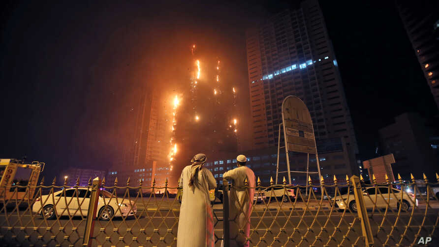 Two Emirati officials watch a high-rise building as a fire spreads up the side of the building in Ajman, United Arab Emirates, March 29, 2016.