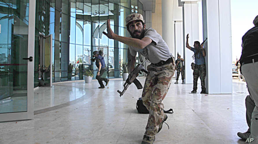 Rebel fighters and a television cameraman take shelter as an intense gun battle erupted outside the Corinthia hotel, where many foreign journalists are staying, in Tripoli, Libya, August 25, 2011