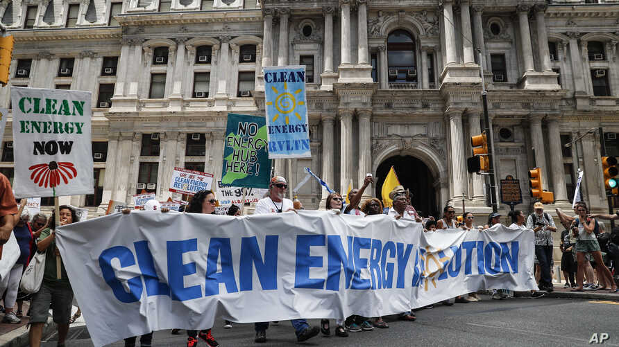 Climate change activists carry signs as they march during a protest in downtown Philadelphia ahead of the Democratic National Convention, July 24, 2016.