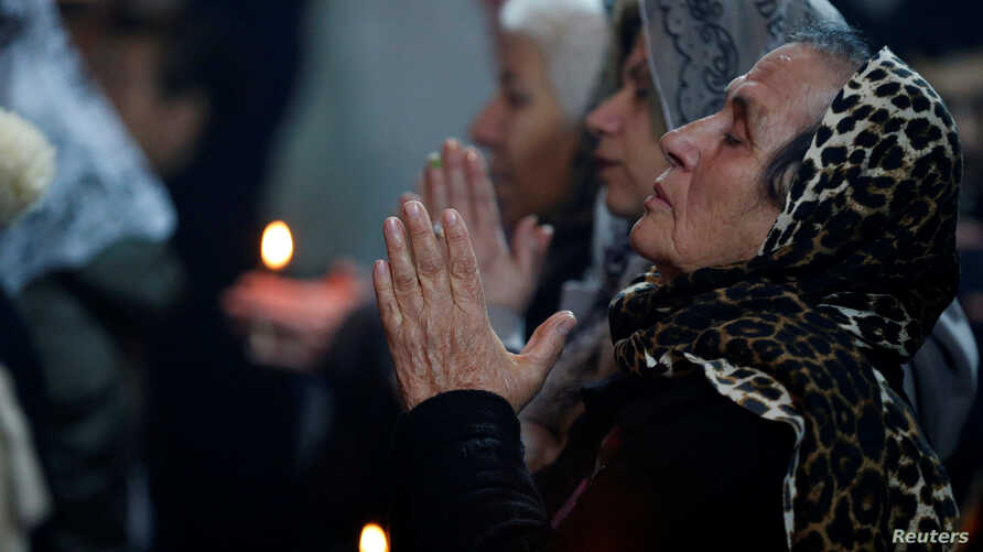 Iraqi Christians attend a Mass on Christmas eve at the Mar Shimoni church in the town of Bartella, east of Mosul, Dec. 24, 2016.