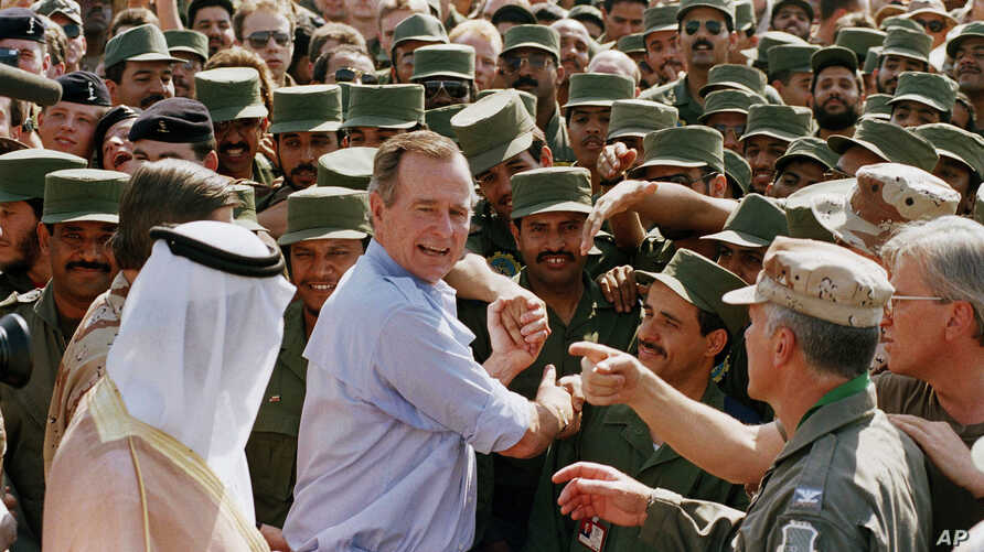 President George H.W. Bush is greeted by Saudi troops and others as he arrives in Dhahran, Saudi Arabia, for a Thanksgiving visit, Nov. 22, 1990. Bush died at the age of 94 on Friday, Nov. 30, 2018, about eight months after the death of his wife, Bar