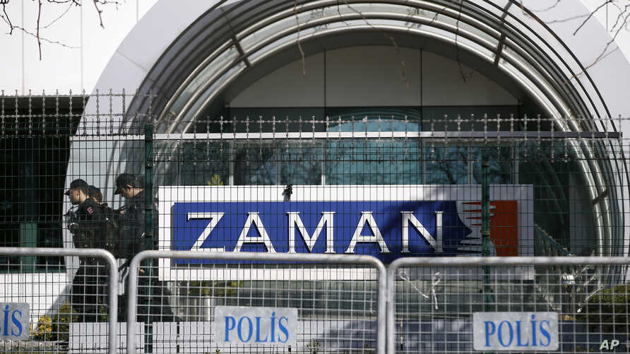 Riot police officers walk by the headquarters of Zaman newspaper in Istanbul, Turkey, March 6, 2016.