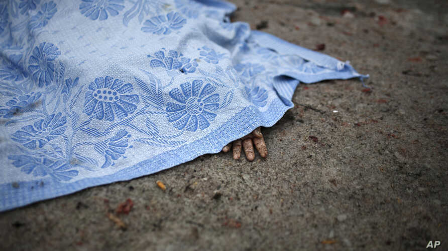A body of a civilian killed in shelling is covered by a blanket in Donetsk, eastern Ukraine, Jan. 30, 2015.