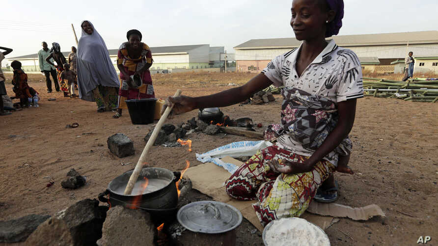 FILE - An unidentified woman who fled her home following an attack by Islamist militants, in Mubi, prepares a meal at the camp for internally displaced people in Yola, Nigeria.