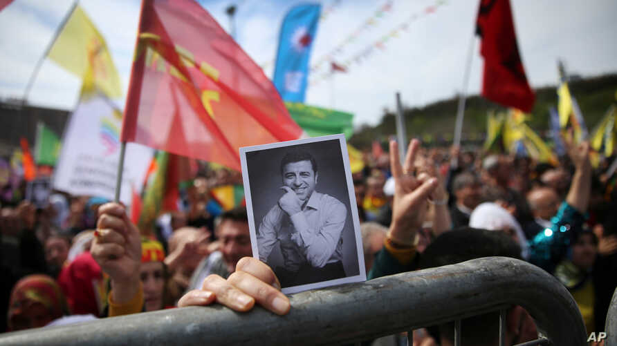 FILE - A woman holds a photograph of former co-leader of pro-Kurdish Peoples' Democratic Party, or HDP, Selahattin Demirtas, during the Newroz celebrations, marking the start of spring, in Istanbul, March 21, 2018.