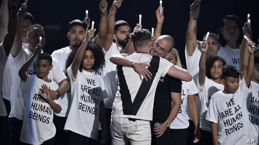 """Ryan Tedder of One Republic, left, and Logic embrace after performing """"One Day"""" onstage at the MTV Video Music Awards at Radio City Music Hall on Monday, Aug. 20, 2018, in New York."""