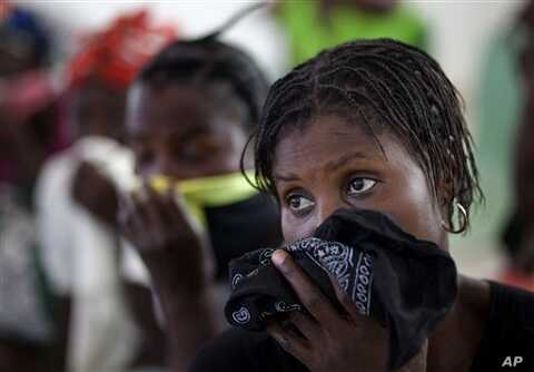 Women cover their mouths and noses as they wait for their children suffering cholera symptoms to be treated at the hospital in Grande-Saline, Haiti, Saturday, Oct. 23, 2010. A spreading cholera outbreak in rural Haiti threatened to outpace aid groups