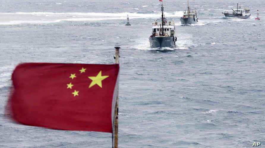 Chinese fishing boats sail in the lagoon of Meiji reef off the island province of Hainan in the South China Sea, July 20, 2012.