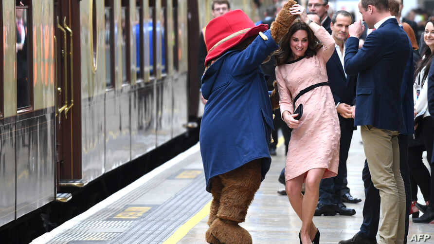 Britain's Catherine, Duchess of Cambridge, (C) dances with a person in a Paddington Bear outfit by her husband Britain's Prince William, Duke of Cambridge as they attend a charities forum event at Paddington train station in London on October 16, 201
