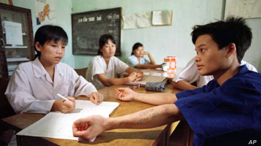 Doctors at a drug rehabilitation clinic check for any signs that Ha Van Canh, 19, has been injecting himself with drugs in this file photo taken on July 30, 1997.
