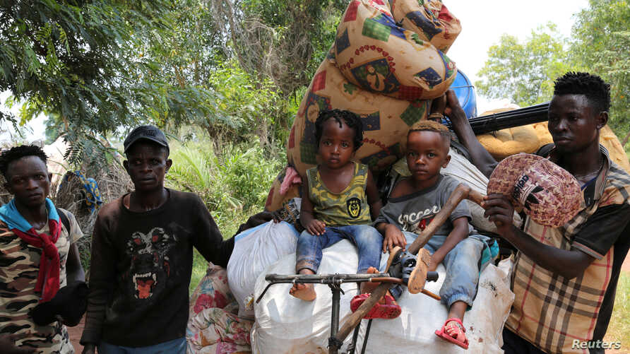 Congolese migrants expelled from Angola push a rented bicycle to transport their children and belongings along the road to Tshikapa, Kasai province near the border with Angola, in the Democratic Republic of the Congo, Oct. 12, 2018.