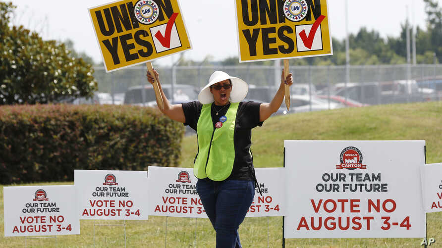 A UAW supporter sings as she tries to beat the hot sun outside an employee vehicle entrance at the Nissan vehicle assembly plant in Canton, Miss., Aug. 4, 2017.