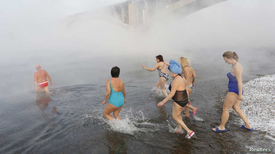 Women follow Mikhail Sashko (L), chairman and one of the founders of the Cryophile winter swimmers club, during a celebration of his 68th birthday in the Yenisei River in the Siberian city of Krasnoyarsk, Russia, Nov. 21, 2015.