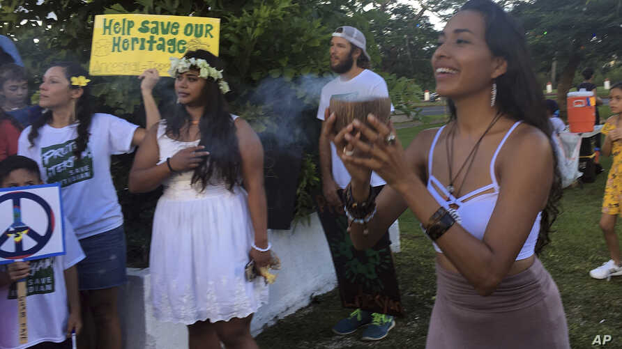 Eva Aguon Cruz, 30, holds a cup with burned flower as a ritual to call for protections from the spirits as about a hundred people gather at Chief Kepuha Park in Hagatna, Guam, for a rally for peace, Aug. 14, 2017. The threatened missile attack by Nor