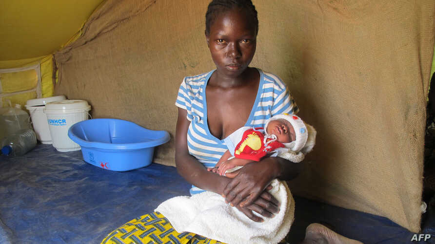 A woman from the Central African Republic (CAR) holds her baby in a refugee camp set up by the UNHCR in Nangungue, eastern Cameroon, April 12, 2013.
