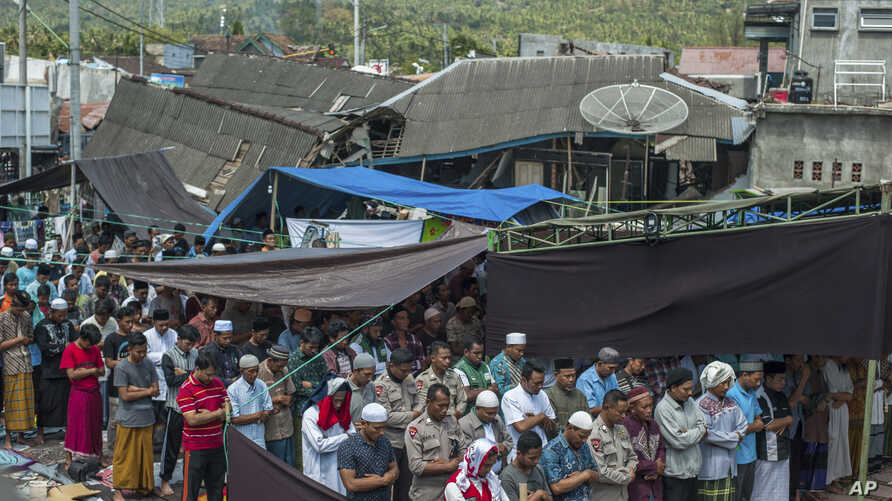 Muslim men perform Friday prayer as houses ruined by Sunday's earthquake are seen in the background at a makeshift mosque in Pamenang, Lombok Island, Indonesia, Aug. 10, 2018.