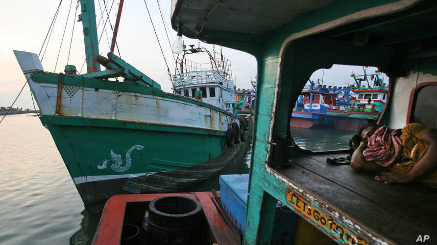 A fisherman sleeps on his boat as the vessel, left, used to carry Rohingya Muslims from Myanmar and migrants from Bangladesh is docked at a port in Lhokseumawe, Aceh province, Indonesia, Thursday, May 14, 2015.