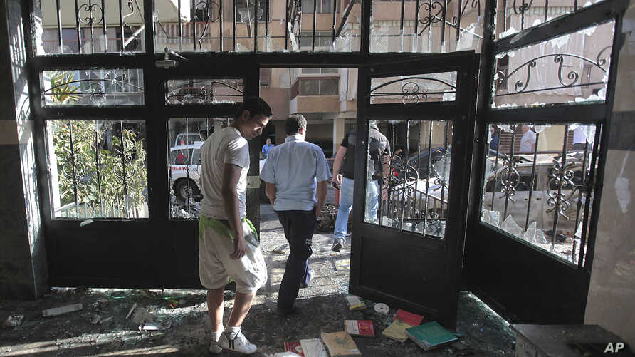 Lebanese citizens leave a destroyed building that was damaged during clashes erupted between pro- and anti-Syrian Sunni groups, in Beirut, Lebanon, May 21, 2012.