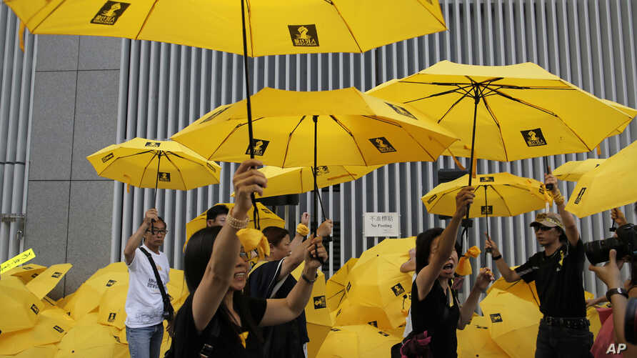 """Protesters raise yellow umbrellas during a rally to mark the one year anniversary of """"Umbrella Movement"""" outside the government headquarters in Hong Kong, Sept. 28, 2015."""