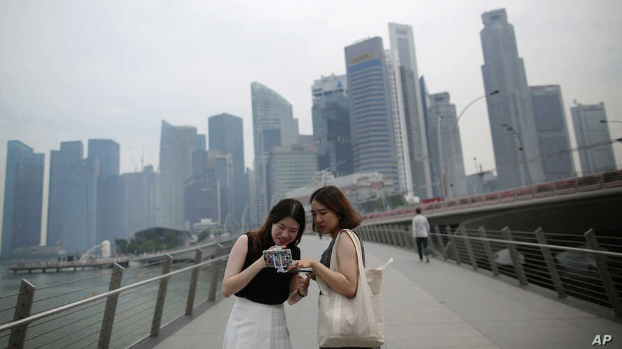 Tourists look at photographs taken on their smartphones in front of a hazy financial skyline in Singapore on Friday, Aug. 26, 2016.