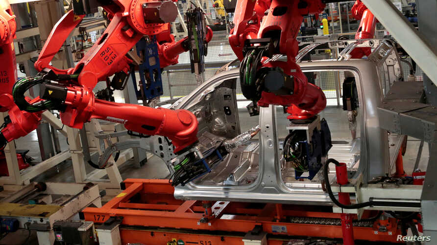 FILE - Robots work on the cab of a 2019 Ram pickup at the Fiat Chrysler Automobiles Sterling Heights Assembly Plant in Sterling Heights, Mich., Oct. 22, 2018.