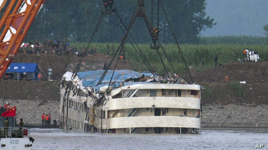 Rescuers watch the capsized ship Eastern Star being lifted by cranes on the Yangtze River in Jianli county of southern China's Hubei province, as seen from across the river from Huarong county of southern China's Hunan province, June 5, 2015.