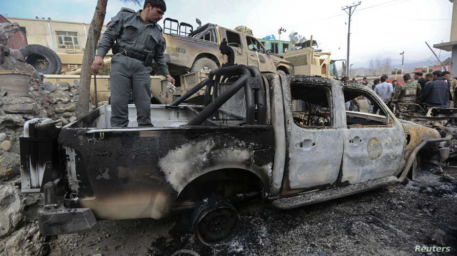 An Afghan policeman inspects a damaged vehicle at the site of a complex suicide attack in Sarobi district, east of Kabul, Feb. 21, 2014.