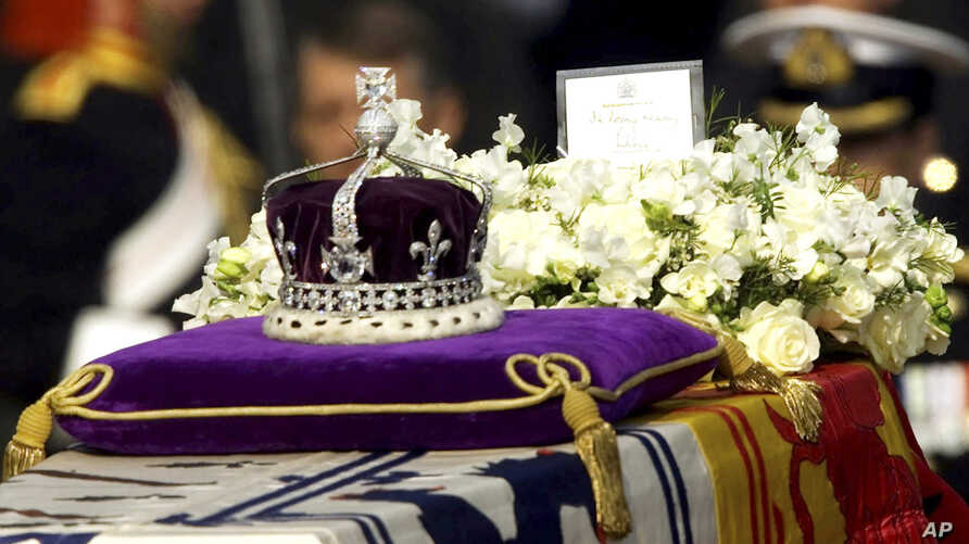 """FILE - The Koh-i-noor, or """"mountain of light,"""" diamond, set in the Maltese Cross at the front of the crown made for Britain's late Queen Mother Elizabeth, is seen on her coffin, along with her personal standard, a wreath and a note from her daughter,"""