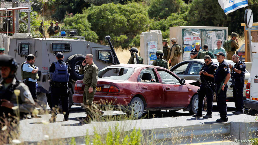 Israeli security forces gather at the scene where a female Palestinian was shot dead by Israeli troops at the entrance to Kiryat Arba near the West Bank city of Hebron, June 24, 2016.