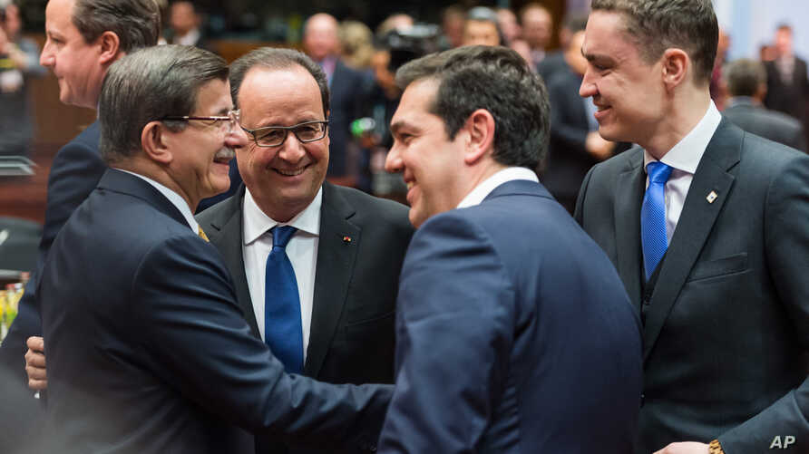 Turkish Prime Minister Ahmet Davutoglu, left, speaks with, from left, French President Francois Hollande, Greek Prime Minister Alexis Tsipras and Estonian Prime Minister Taavi Roivas during a round table meeting at an EU summit in Brussels, March 18,