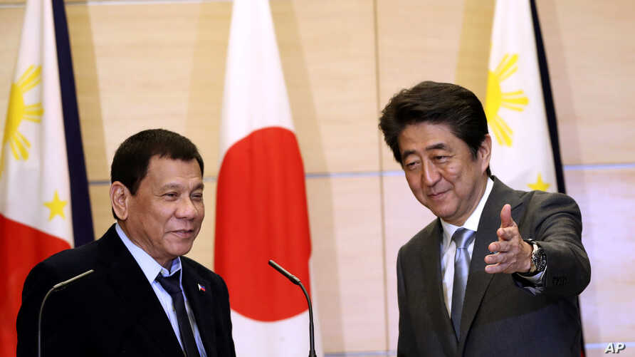 Philippine President Rodrigo Duterte, left, is shown the way by Japanese Prime Minister Shinzo Abe after a joint press conference following their meeting at Abe's official residence in Tokyo, Oct. 26, 2016.