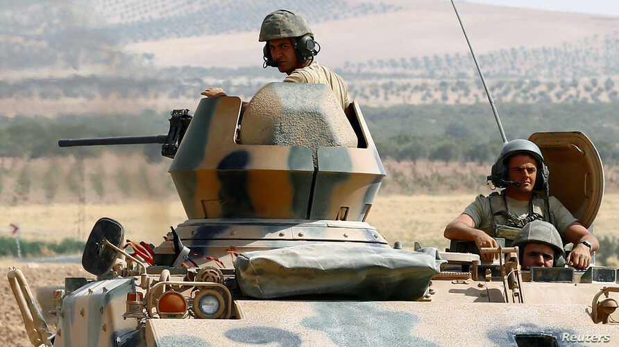 Turkish soldiers on an armored personnel carrier escort a military convoy on a main road in Karkamis on the Turkish-Syrian border in the southeastern Gaziantep province, Turkey, August 26, 2016.