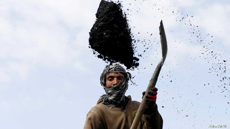 A laborer unloads coal from a truck at a coal dump site on the outskirts of Kabul, Afghanistan March 7, 2017.