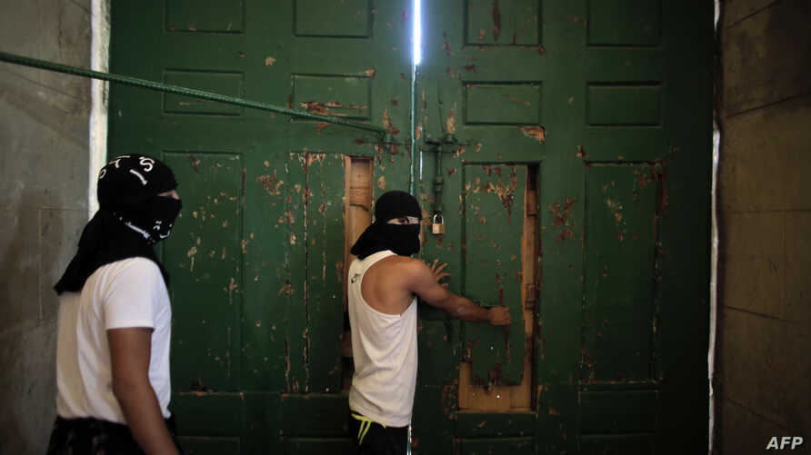 Masked Palestinians secure the door of Jerusalem's Al-Aqsa Mosque, one of Islam's holiest sites, Sept. 27, 2015, as they plan to remain inside to protect it in case of clashes.