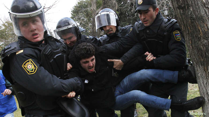 "FILE - Police officers detain a man during a rally in Baku, Azerbaijan, Jan. 26, 2013. In addition to arresting 20 political and youth activists in 2016 on ""spurious charges,"" the Azeri government has severely limited the ability of independent group"