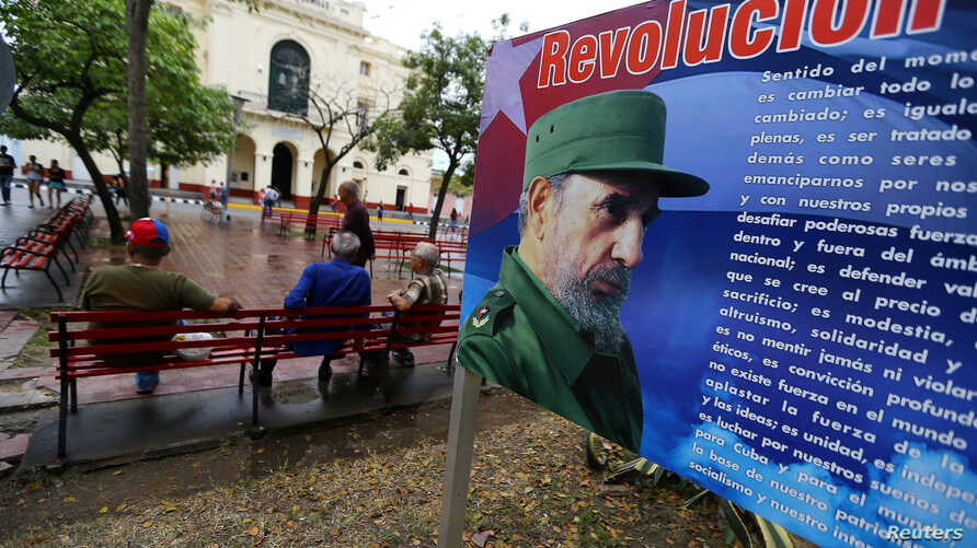 People sit in front of a billboard with a message about Cuba's late President Fidel Castro in Santa Clara, Cuba, Nov. 30, 2016.