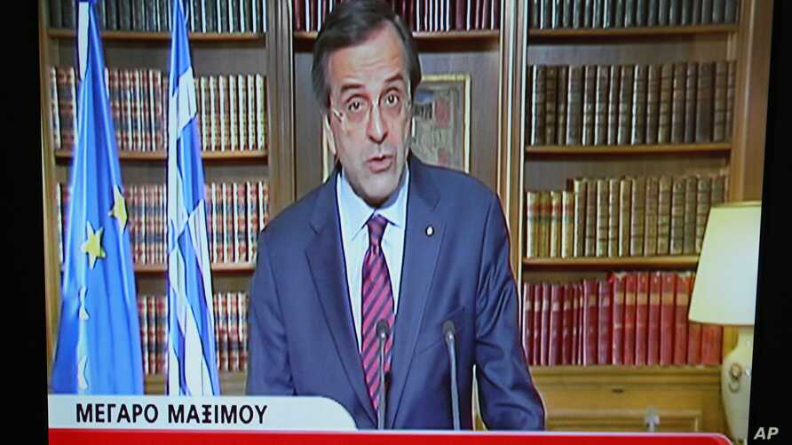 In this image taken from NET state television channel Greece's Prime Minister Antonis Samaras makes an announcement to the Greek people from his office in Athens, April 15, 2013.