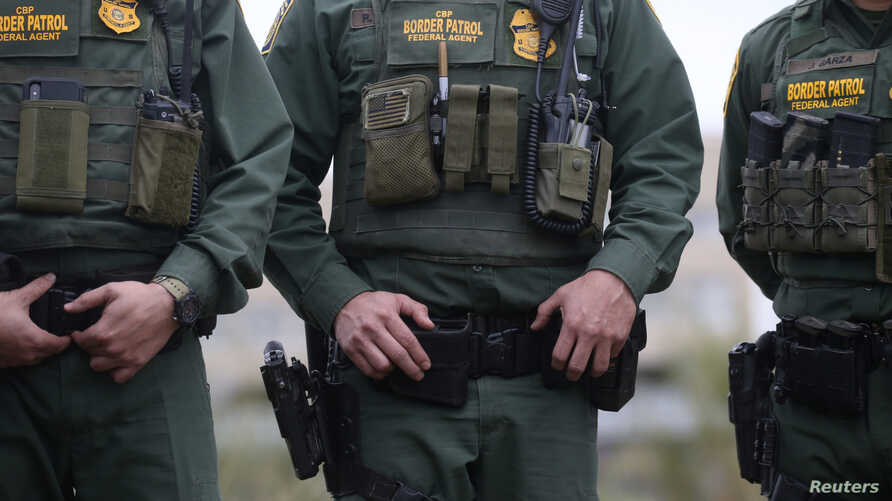 U.S. Customs and Border Patrol agents watch as President Donald Trump visits the banks of the Rio Grande River in Mission, Texas, Jan. 10, 2019.