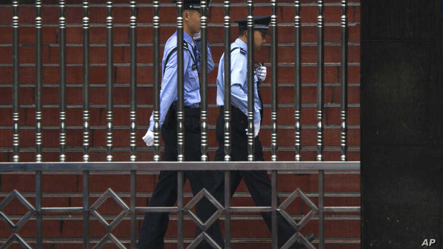 FILE - Chinese policemen are seen on patrol in southwest China's Sichuan province, Sept. 24, 2012. A police report on the death of a 14-year-old student whose body was found outside his dormitory at Taifu Middle School in Luzhou, Sichuan province, ha