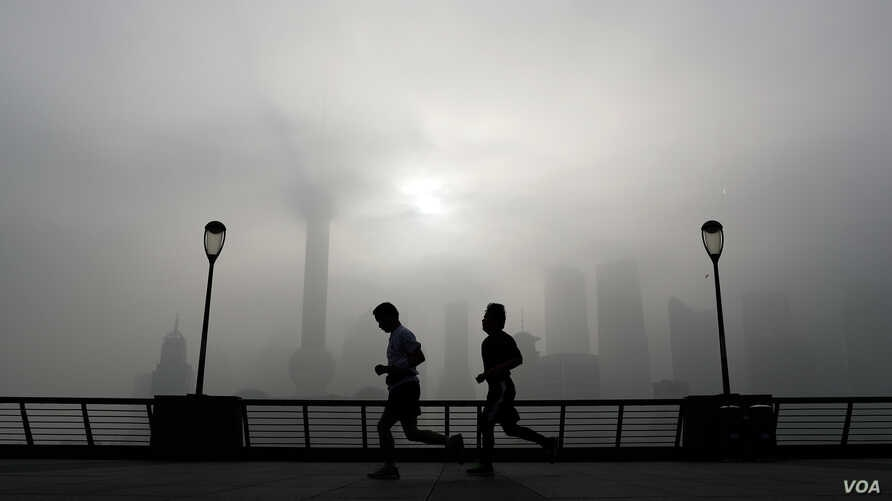 People jog past the Pudong Financial District shrouded with fog and pollution at the Shanghai Bund in Shanghai, China, Thursday, April 14, 2016.