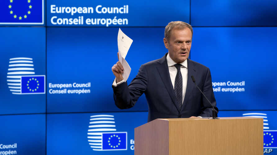 European Council President Donald Tusk holds up the document from the UK during a media conference at the Europa building in Brussels, March 29, 2017. Tusk has received a letter from British Prime Minister Theresa May, invoking Article 50 of the bloc