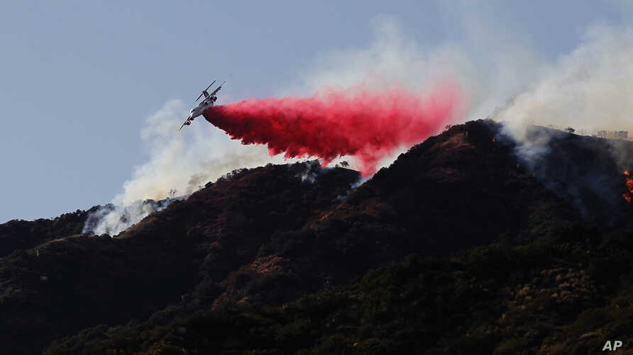 A firefighting plane makes a retardant drop on a hill near a wildfire in Azusa, Calif., June 20, 2016.